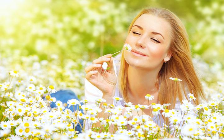 Женщина нюхает цветок